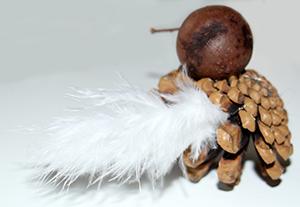 Coller une plume de chaque côté de la pomme de pin