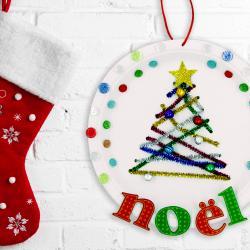 Découvrez un bricolage facile et coloré qui permettra aux enfants de fabriquer une jolie suspension de Noël pour décorer la maison ! Pour ce bricolage vous n'aurez besoin que de matériel simple : assiette en carton, chenilles, boutons...