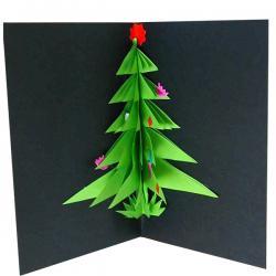 Réalisation d'une carte de voeux avec un gros sapin en relief. Le sapin est découpé dans du papier vert puis il est collé sur la carte.