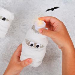 Voici une superbe lanterne momie à fabriquer pour Halloween avec les enfants ! Il vous suffira d'un bocal en verre, d'un peu de bandage et de colle pour la réaliser.