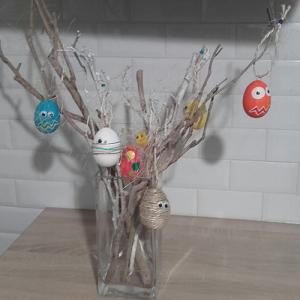Suspendre des oeufs décorés comme des monstres à des branches pour faire un arbre de Pâques pour les enfants