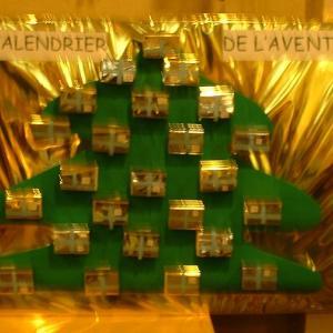 Bricolage d'un calendrier de l'avent sapin sur lequel des petites boîtes à cadeau sont collées. Le calendrier de l'Avent aide les enfants à attendre le jour de Noël.