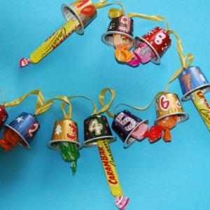 Réaliser une guirlande pour attendre Noël en comptant les jours de décembre. Cette guirlande calendrier est réalisée avec des capsules à café évidées, numerot
