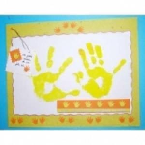 Réaliser une composition de scrapbooking pour mettre en scène l'empreinte des mains de l'enfant