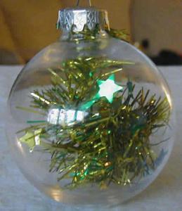 Fabriquer des boules de Noël transformables. Il suffit de les ouvrir pour les transformer. Des boules en plastiques sont remplies de petites décorations.