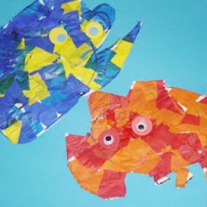 Réaliser le collage d'un poisson réalisé avec du papier vitrail découpé et collé. Réalisation d'un tableau de poissons. Les poissons sont décorés de morceau