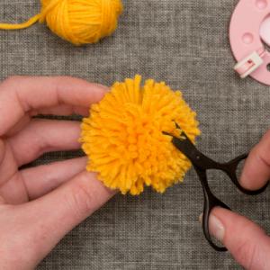 Mode d'emploi pour réaliser des pompons ronds en laine. Les pompons serviront à la décoration.Retrouver cette activité intemporelle et fabriquer des pompons pour la décoration, les bricolages ou les d
