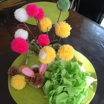 Des fleurs en pompons, un lapin en pompons et une fleur en crépon pour un joli décor de Pâques