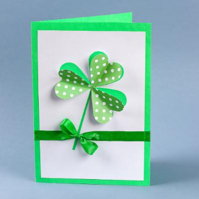 Une carte de la Saint à Patrick décorée d'un trèfle à fabriquer avec les enfants.